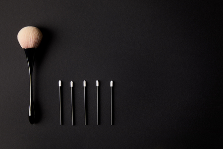 top view of one big and five small makeup brushes on black background