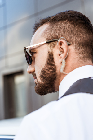 side view of handsome security guard with security earpiece on street