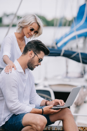 side view of smiling girl looking at handsome man in sunglasses using laptop on yacht Stock fotó