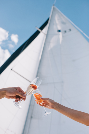 cropped image of boyfriend and girlfriend clinking by glasses with champagne on yacht Stock fotó
