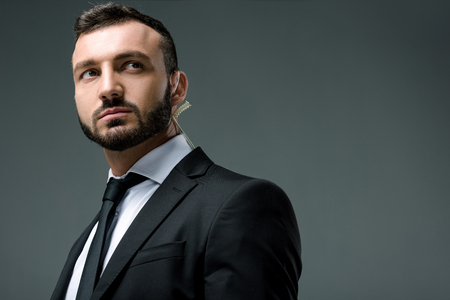 handsome security guard with security earpiece looking away isolated on grey