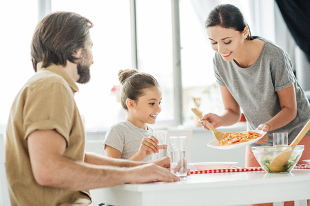 smiling young mother with tasty breakfast for daughter and husband at kitchen Foto de archivo