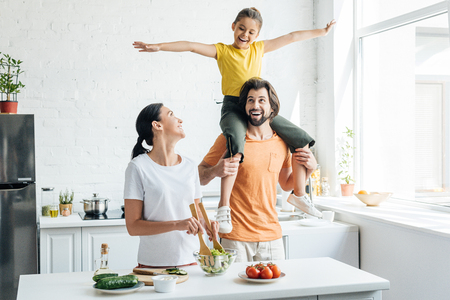 beautiful young woman preparing salad while her daughter riding on shoulders of husband at kitchen