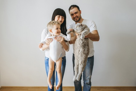 portrait of happy parents holding little toddler boy and grey cat at home Standard-Bild - 106151265