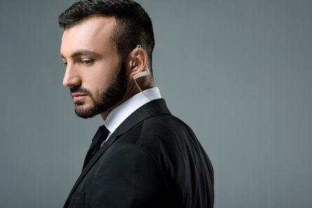 side view of handsome security guard with security earpiece isolated on grey