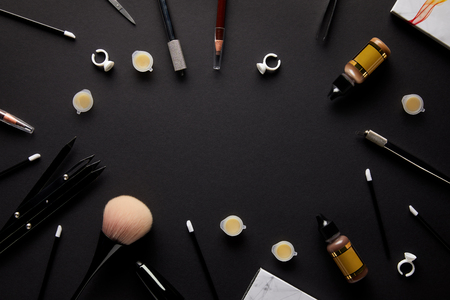 top view of tools for permanent makeup on black tabletop in salon