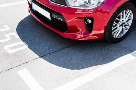 Close-up view of red car on street parking lot Stok Fotoğraf