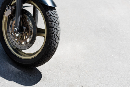 Front wheel with black tire of motorcycle on street Banco de Imagens