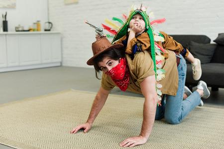 Vater und kleiner Sohn in Kostümen spielen zu Hause zusammen