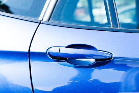 Close-up view of handle in blue car door