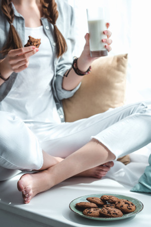 cropped view of girl eating cookies with milk