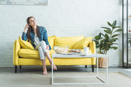 pensive smiling girl sitting on sofa and looking away at home Stock Photo