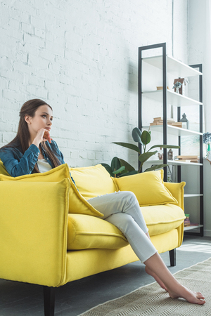 beautiful pensive barefoot girl sitting on sofa and looking away at home