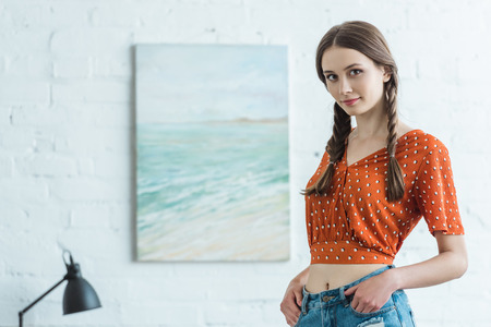 beautiful teen girl with braids standing in room with painting on wall