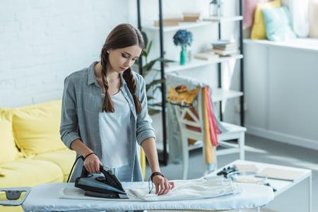 hermosa mujer joven planchar pantalones blancos en casa