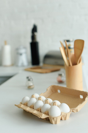 close up view of raw chicken eggs in box on tabletop in kitchen Banco de Imagens