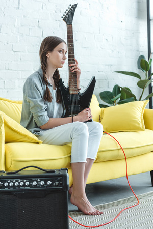 teen girl sitting on sofa with electric guitar and loud speaker Foto de archivo