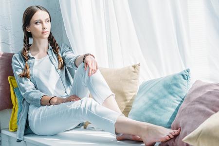 doordachte tiener meisje zittend op de vensterbank met gezellige kussens
