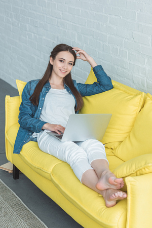 high angle view of beautiful girl using laptop and smiling at camera while sitting on sofa at home