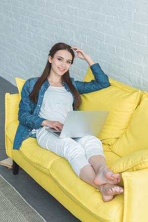 wysoki kąt widzenia pięknej dziewczyny korzystającej z laptopa i uśmiechającego się do kamery, siedząc na kanapie w domu Zdjęcie Seryjne