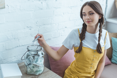 beautiful teen girl putting dollar banknote into saving glass jar