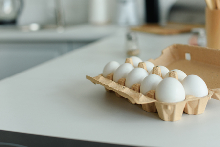 close up view of raw chicken eggs in box on tabletop in kitchen Stock Photo