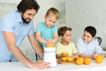 family making fresh orange juice together in kitchen at home