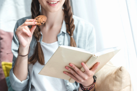 cropped view of girl reading book and eating cookie Stock Photo