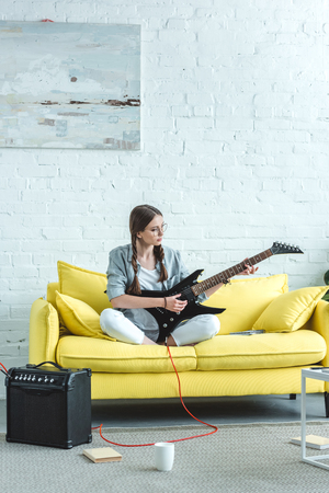 beautiful teen girl playing electric guitar on sofa in living room