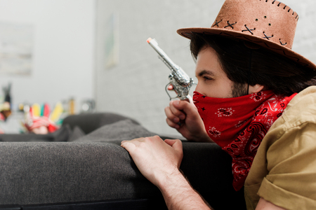 side view of man in red bandana and cowboy hat with toy gun at sofa at home Фото со стока