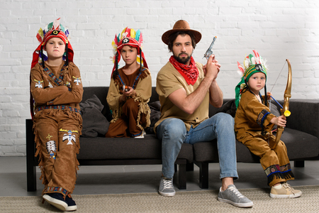 father in hat and red bandana sitting on sofa with little sons in indigenous costumes at home Stok Fotoğraf