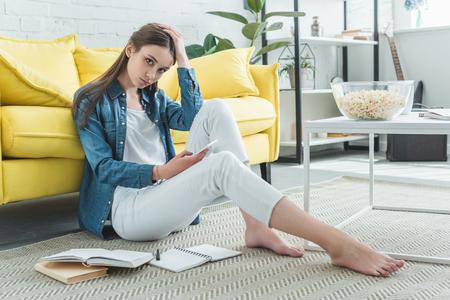 znudzona nastolatka trzymająca smartfon i patrząca w kamerę siedząc na dywanie i ucząc się w domu