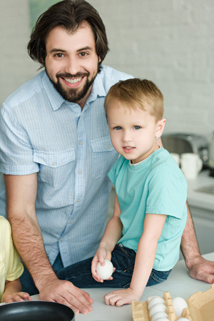 portrait of smiling father and little son with raw egg in hand in kitchen at home Banco de Imagens