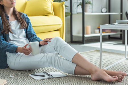 cropped shot of barefoot girl holding cup while sitting on carpet and studying at home