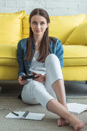 beautiful teenage girl sitting on carpet and playing with joystick