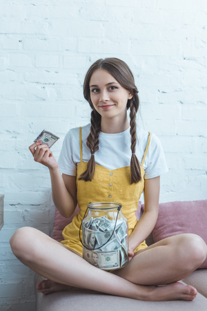 female teenager putting dollar banknote into glass jar for saving while sitting on sofa Foto de archivo