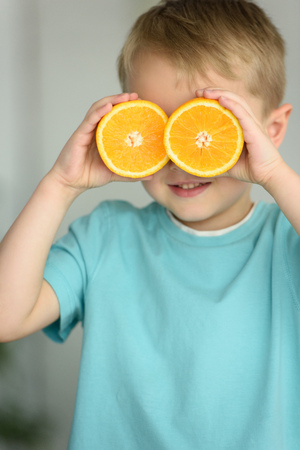 obscured view of little boy covering eyes with pieces of fresh orange in hands Stok Fotoğraf - 106154346