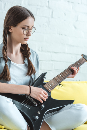 attractive teen girl playing black electric guitar on sofa