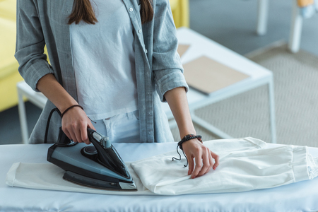 cropped view of girl ironing white pants at home Foto de archivo