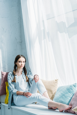 beautiful female teenager sitting on windowsill with pillows