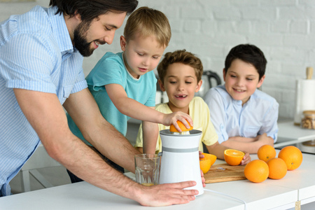 happy family making fresh orange juice in kitchen at home