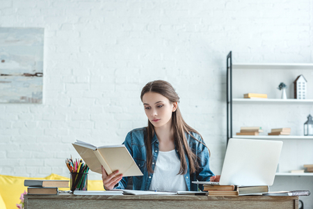 concentrated girl reading book and using laptop while studying at home Imagens