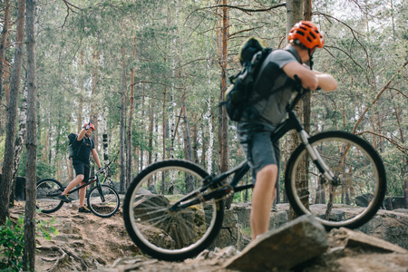 male extreme cyclist on mountain bike showing thumb up gesture to friend with bmx in forest