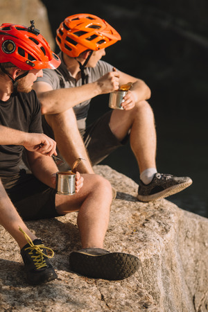 active travellers eating canned food on rocky cliff Zdjęcie Seryjne