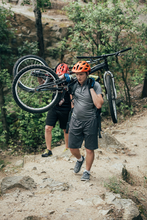 two male extreme cyclists in helmets carrying mountain bikes in forest