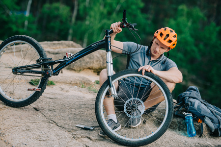 young trial biker attaching wheel to bicycle outdoors