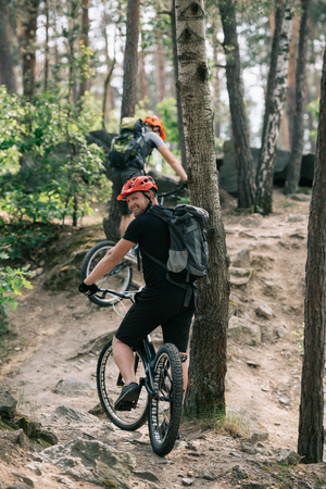 smiling male extreme cyclist riding on mountain bicycle with friend in forest