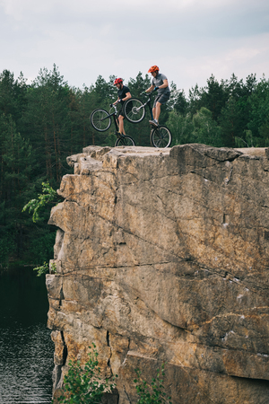 two male extreme cyclists in protective helmets jumping on mountain bicycles on rocky cliff in forest