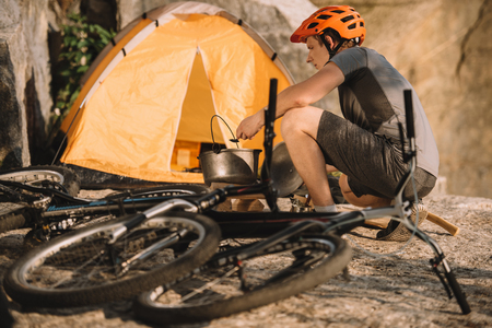 young trial biker at camping with bicycles outdoors Фото со стока