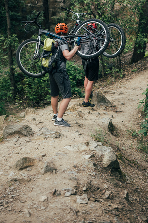 rear view of two male extreme cyclists in helmets carrying mountain bikes in forest